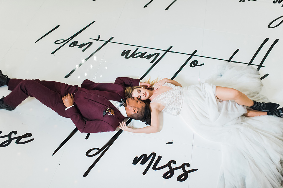 rock-n-roll-wedding-style-bride-and-groom-laying-on-ground-bride-in-a-white-flowing-gown-and-a-black-leather-jacket-groom-in-a-deep-burgundy-suit-with-floral-bow-tie