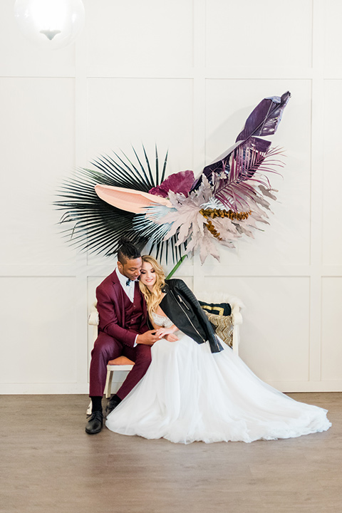 rock-n-roll-wedding-style-bride-and-groom-sitting-on-white-couch-bride-in-a-white-flowing-gown-and-a-black-leather-jacket-groom-in-a-deep-burgundy-suit-with-floral-bow-tie