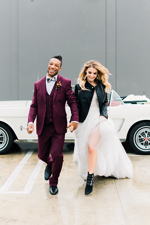 rock-n-roll-wedding-style-bride-and-groom-walking-bride-in-a-white-flowing-gown-and-a-black-leather-jacket-groom-in-a-deep-burgundy-suit-with-floral-bow-tie