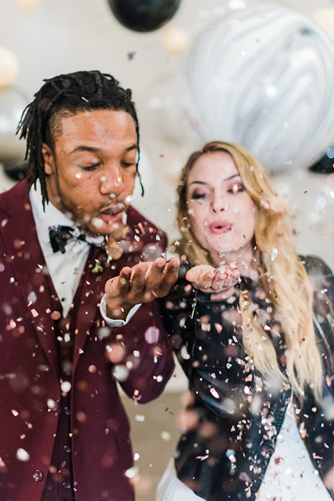 rock-n-roll-wedding-style-bride-and-groom-with-confetti-bride-in-a-white-flowing-gown-and-a-black-leather-jacket-groom-in-a-deep-burgundy-suit-with-floral-bow-tie