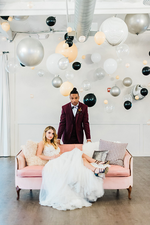 rock-n-roll-wedding-style-bride-on-couch-groom-standing-bride-in-a-white-flowing-gown-and-a-black-leather-jacket-groom-in-a-deep-burgundy-suit-with-floral-bow-tie