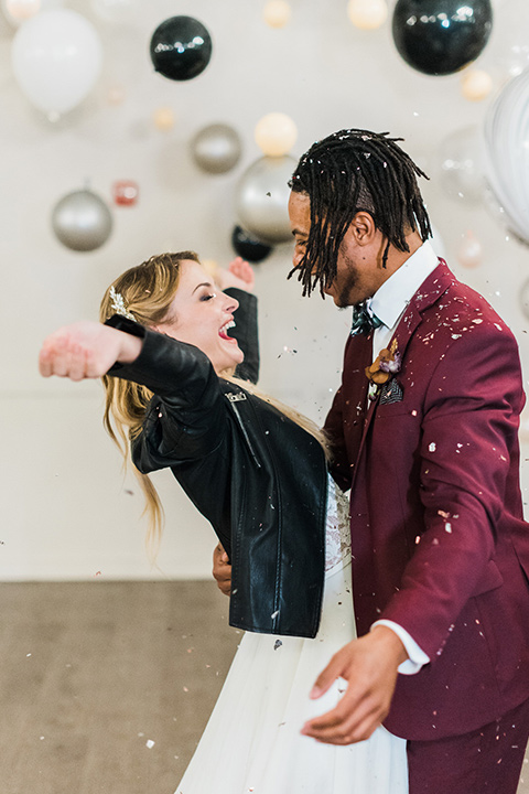 rock-n-roll-wedding-style-bride-with-her-hands-up-groom-smiling-bride-in-a-white-flowing-gown-and-a-black-leather-jacket-groom-in-a-deep-burgundy-suit-with-floral-bow-tie