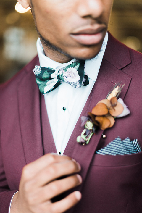 rock-n-roll-wedding-style-close-up-on-menswear-in-a-deep-burgundy-suit-with-floral-bow-tie