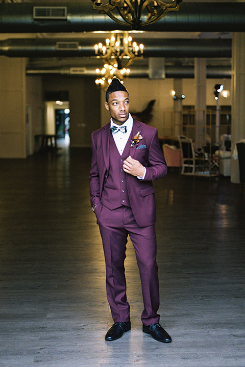 rock-n-roll-wedding-style-groom-standing-in-a-deep-burgundy-suit-with-floral-bow-tie