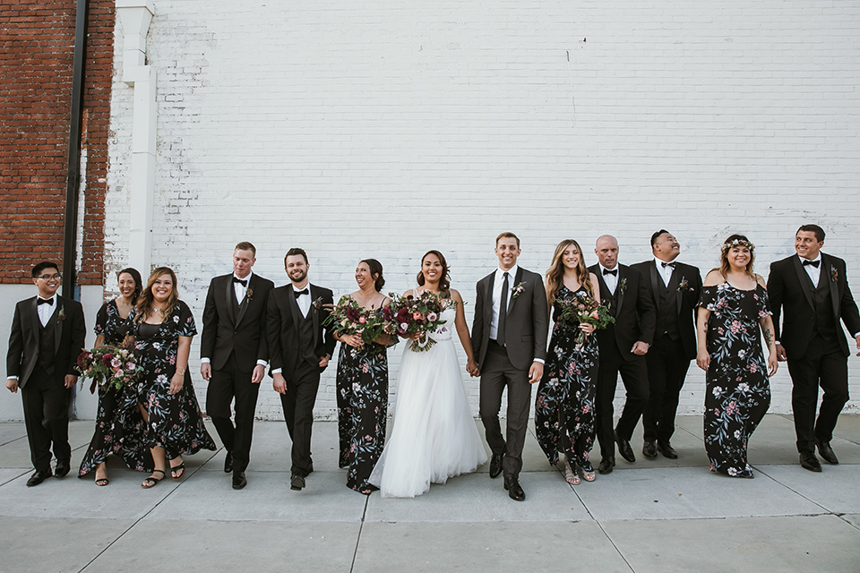 Moniker-Warehouse-Wedding-bridal-party-walking-bridesmaids-in-black-with-pink-floral-long-gowns-the-groomsmen-are-in-black-tuxedos-the-bride-is-in-a-flowing-gown-with-straps-and-a-deep-v-neckline-while-the-groom-wore-a-charcoal-grey-tuxedo-with-a-black-long-tie