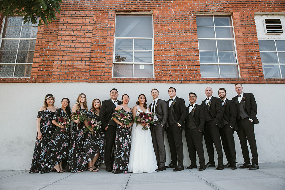 Moniker-Warehouse-Wedding-bridalparty-standing-bridesmaids-in-black-with-pink-floral-long-gowns-the-groomsmen-are-in-black-tuxedos-the-bride-is-in-a-flowing-gown-with-straps-and-a-deep-v-neckline-while-the-groom-wore-a-charcoal-grey-tuxedo-with-a-black-long-tie
