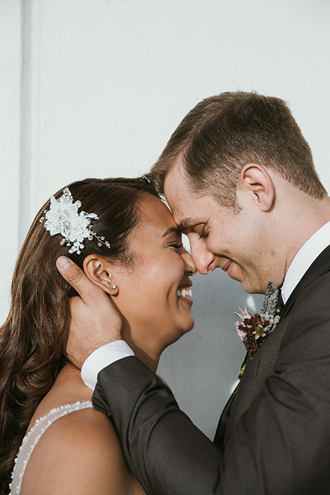Moniker-Warehouse-Wedding-bride-and-groom-close-bride-in-a-flowing-white-gown-with-a-deep-v-neckline-and-straps-the-groom-in-a-charcoal-grey-tuxedo-with-a-black-shawl-lapel