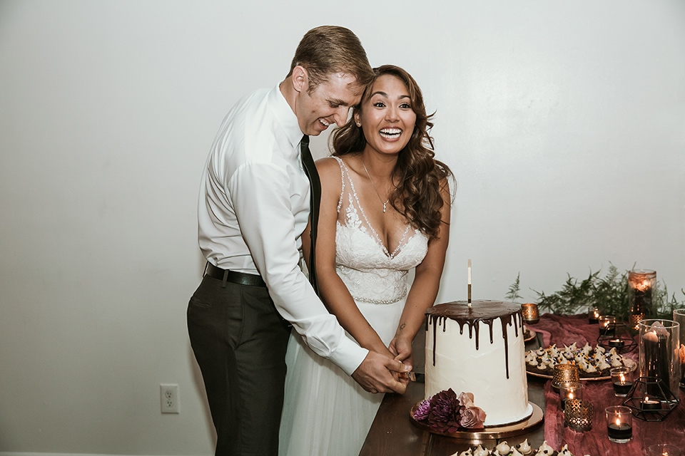 Moniker-Warehouse-Wedding-bride-and-groom-cutting-cake-the-bride-is-in-a-flowing-gown-with-straps-and-a-deep-v-neckline-while-the-groom-wore-a-charcoal-grey-tuxedo-with-a-black-long-tie