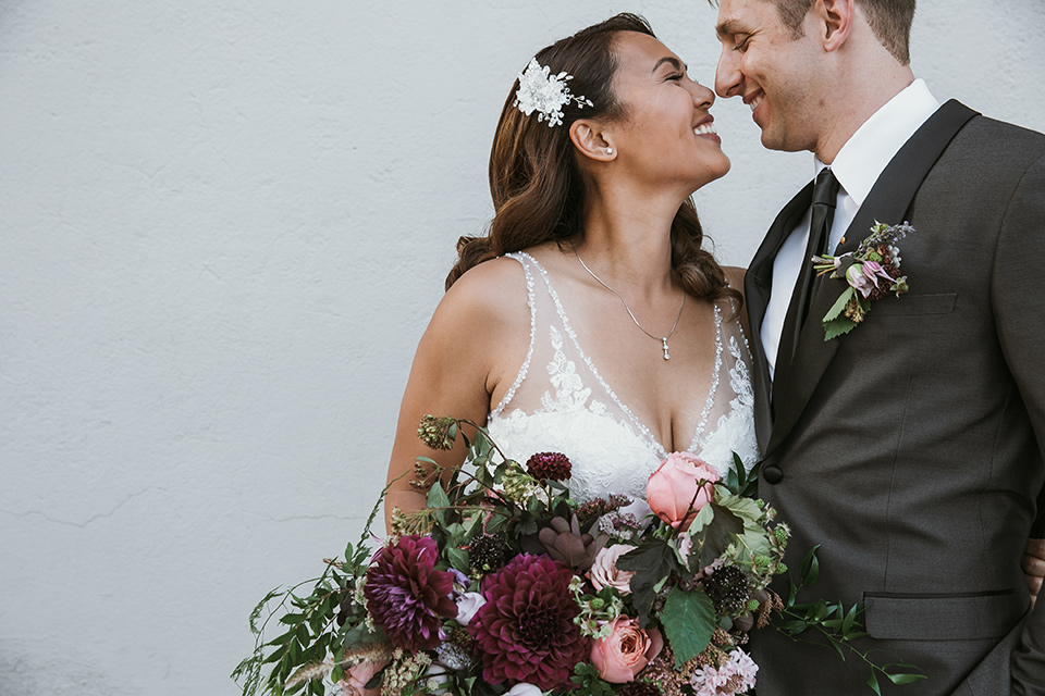 Moniker-Warehouse-Wedding-bride-and-groom-kissing-the-bride-is-in-a-flowing-gown-with-straps-and-a-deep-v-neckline-while-the-groom-wore-a-charcoal-grey-tuxedo-with-a-black-long-tie