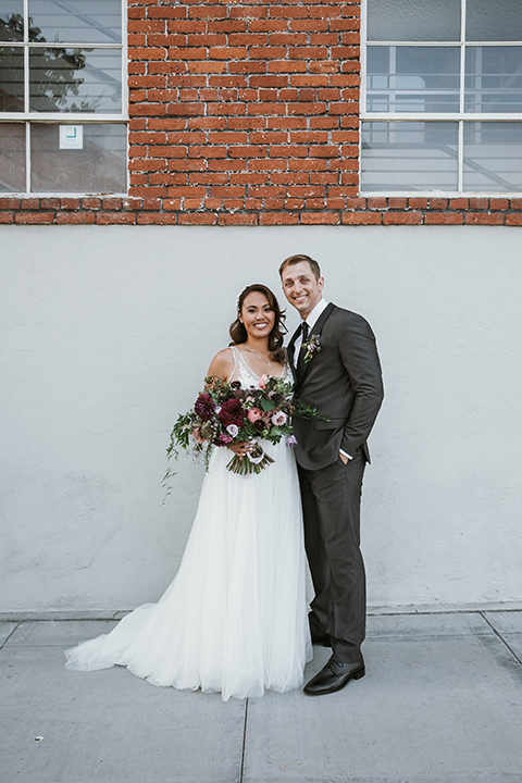 Moniker-Warehouse-Wedding-bride-and-groom-standing-bride-in-a-flowing-white-gown-with-a-deep-v-neckline-and-straps-the-groom-in-a-charcoal-grey-tuxedo-with-a-black-shawl-lapel