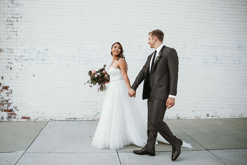 Moniker-Warehouse-Wedding-bride-and-groom-walking-the-bride-is-in-a-flowing-gown-with-straps-and-a-deep-v-neckline-while-the-groom-wore-a-charcoal-grey-tuxedo-with-a-black-long-tie