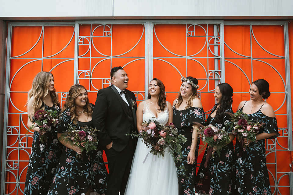 Moniker-Warehouse-Wedding-bridesmaids-and-brideman-bridesmaids-in-black-with-pink-floral-long-gowns-with-a-bridesman-in-a-black-tuxedo-and-the-bride-is-in-a-flowing-gown-with-straps-and-a-deep-v-neckline