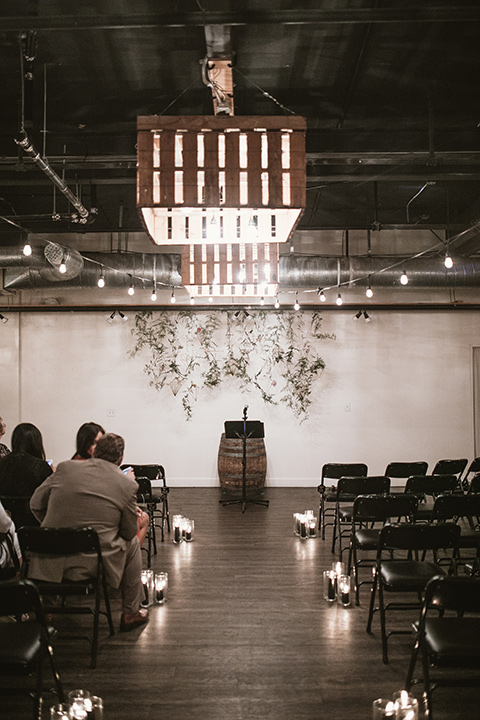 Moniker-Warehouse-Wedding-ceremony-set-up-in-an-industrial-sace-with-concrete-flors-and-dark-lighting-with-romantic-candles-everywhere