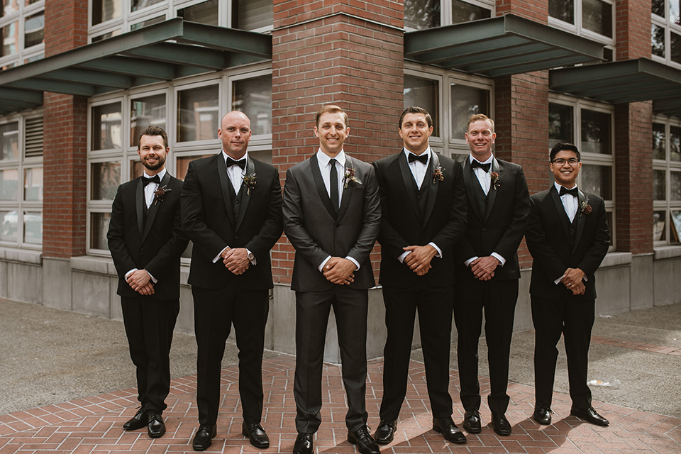 Moniker-Warehouse-Wedding-groomsmen-standing-in-a-line-the-groom-wore-a-charcoal-grey-tuxedo-with-a-black-long-tie-groomsmen-in-black-tuxedos