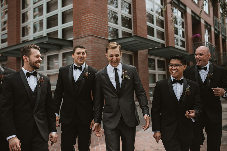 Moniker-Warehouse-Wedding-groomsmen-walking-the-groom-wore-a-charcoal-grey-tuxedo-with-a-black-long-tie-groomsmen-in-black-tuxedos