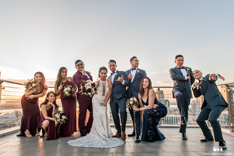 bridesmaids in burgundy gowns and a bridesman in a burgundy suit, the groomsmen in slate blue suits and groomslady in a navy gown