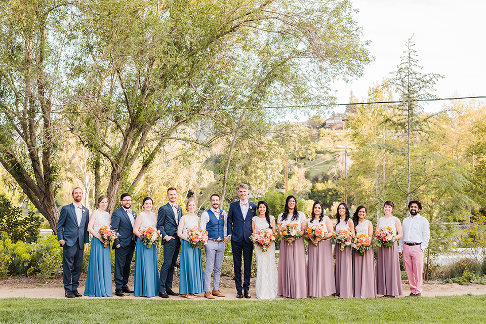 bridesmaids in pink and cream gowns and bridesman in pink pants and white shirt, groomsmen in blue suits and groomsladies in blue skirts and cream tops