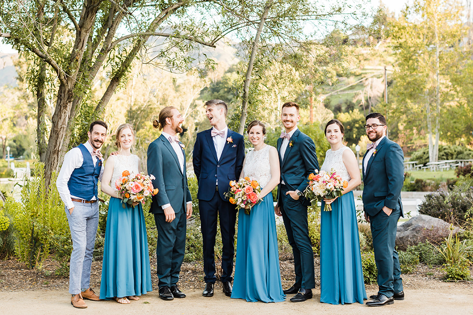 groomsmen in blue suits and groomsladies in blue skirts and cream tops