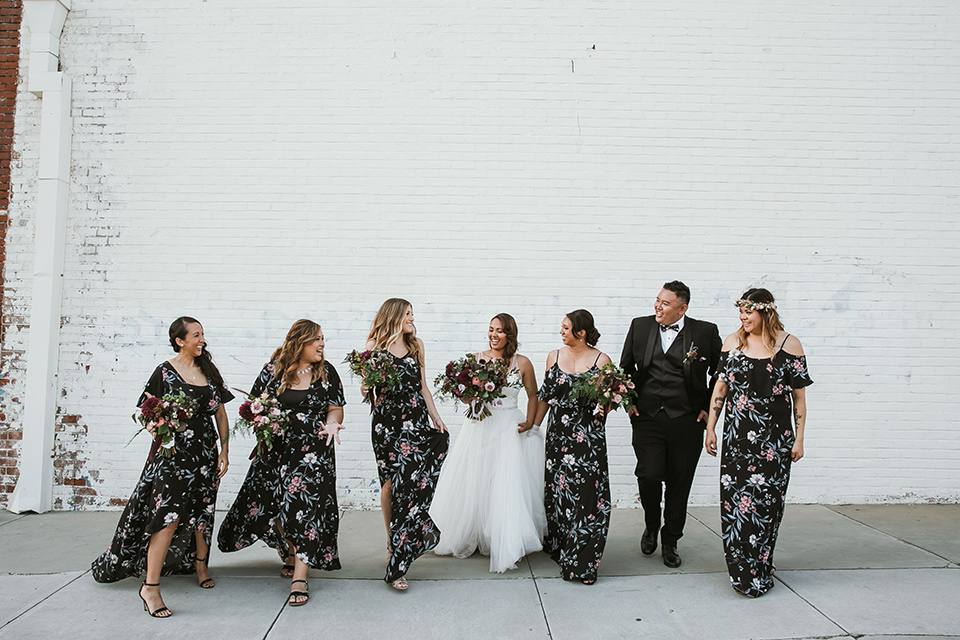 bridesmaids in floral long gowns and bridesman in a black tuxedo