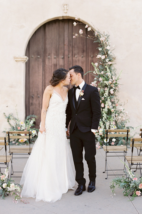 san-gabriel-mission-wedding-shoot-bride-and-groom-after-ceremony-bride-in-a-flowing-gown-with-a-low-back-and-small-straps-the-groom-wearing-a-classic-black-tuxedo-and-bow-tie