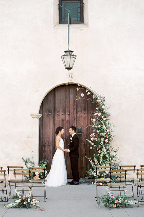 san-gabriel-mission-wedding-shoot-bride-and-groom-at-ceremony-bride-in-a-flowing-gown-with-a-low-cut-back-and-the-groom-wearing-a-black-tuxedo-with-black-bow-tie