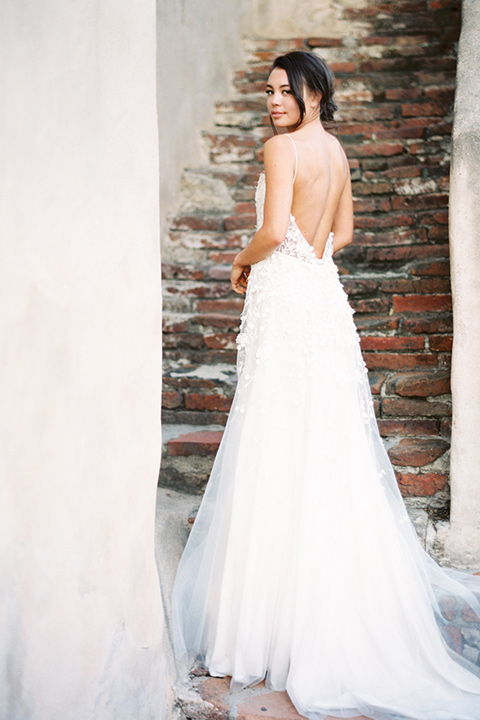 san-gabriel-mission-wedding-shoot-bride-looking-at-camera-bride-in-a-flowing-gown-with-a-low-cut-back