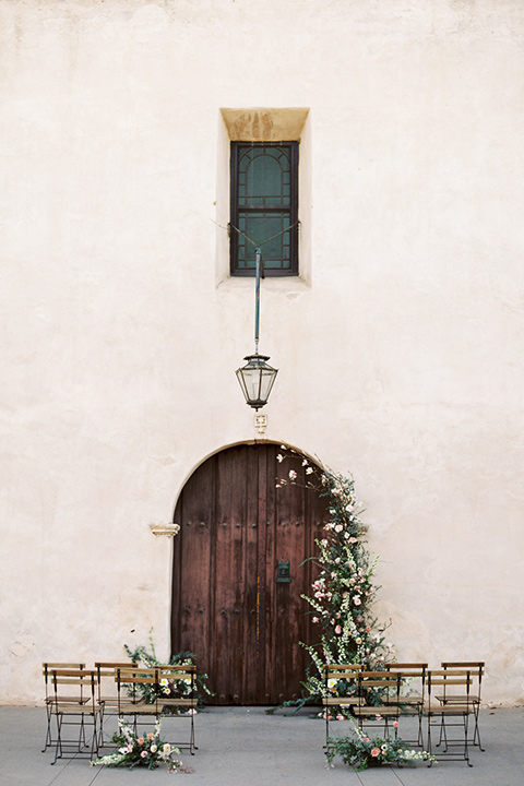 san-gabriel-mission-wedding-shoot-ceremony-space-with-a-big-wooden-door-ad-flowers-all-around-it
