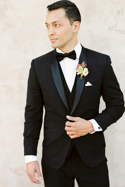 san-gabriel-mission-wedding-shoot-groom-looking-to-the-side-wearing-a-classic-black-tuxedo-and-bow-tie