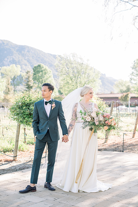 bride in a white ballgown with straps and a deep v neckline and the groom in a dark green suit with a black bow tie