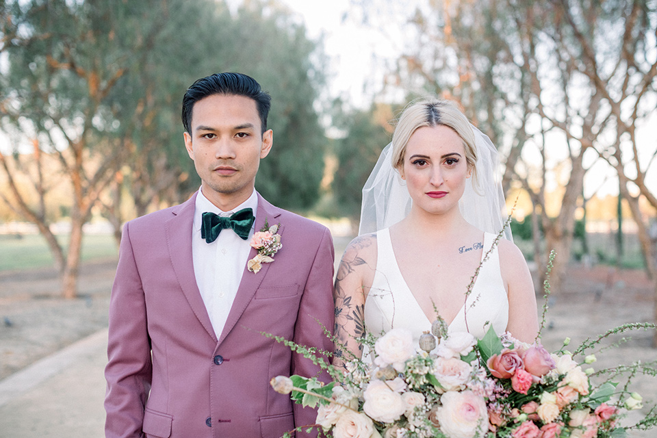 bride in a white ballgown with straps and a deep v neckline and the groom in a pink suit coat with black pants and green velvet bow tie