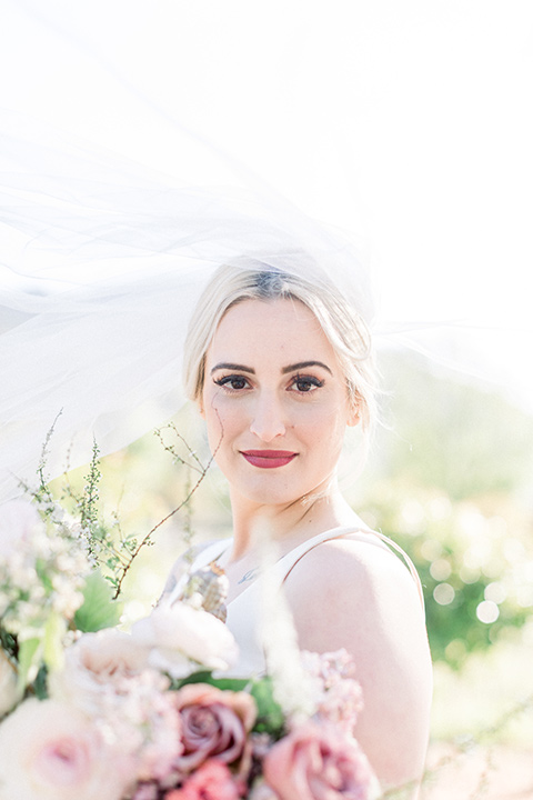 bride in a white ballgown with blonde hair and bright pink lipstick