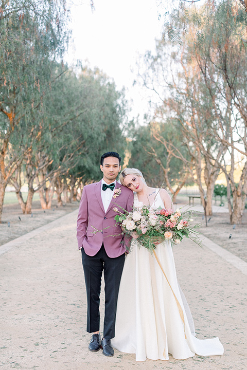 bride in a white ballgown with straps and a deep v neckline and the groom in a pink suit coat, black pants, and a green velvet bow tie