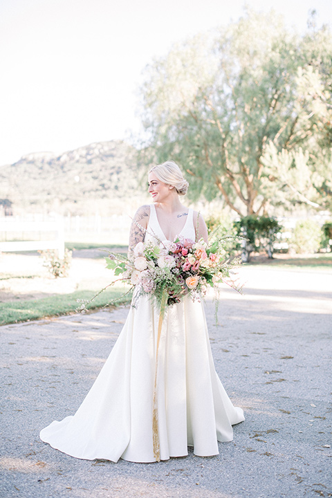 bride in a white ballgown with straps and a deep v neckline
