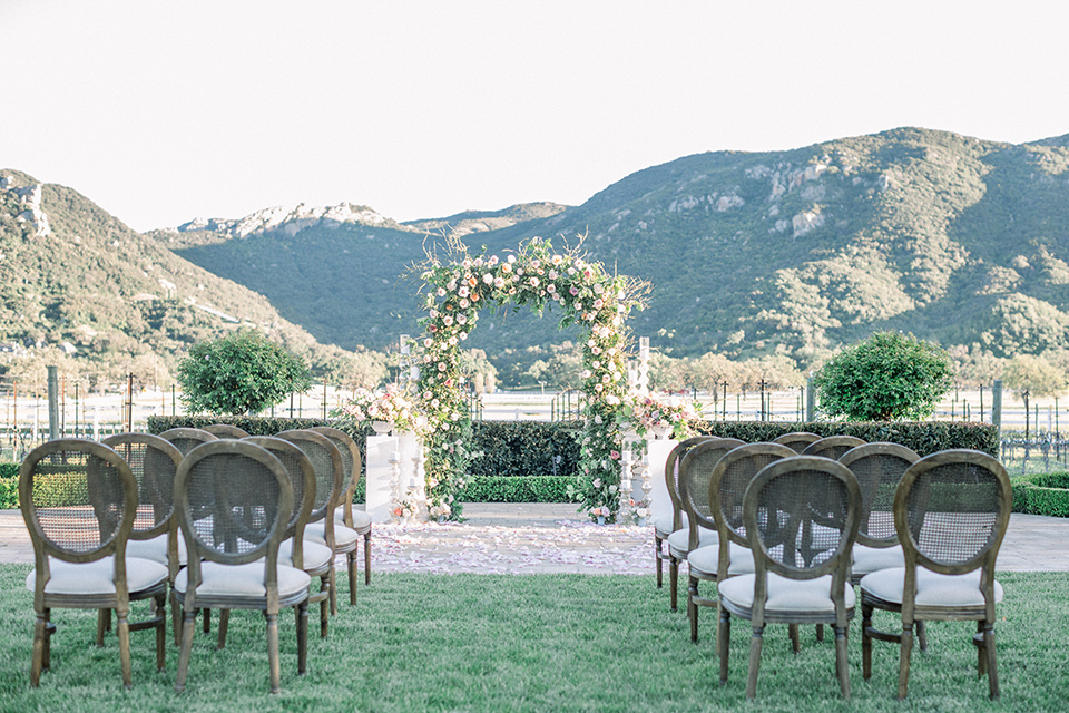 green and white ceremony décor with florals and wooden chairs
