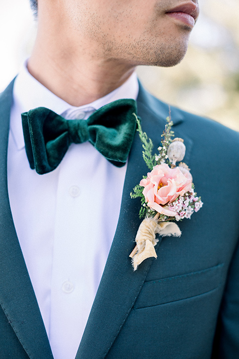 groom in a dark green suit with a black bow tie