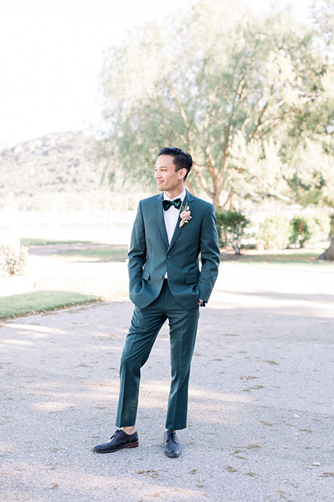 the groom in a dark green suit with a black bow tie