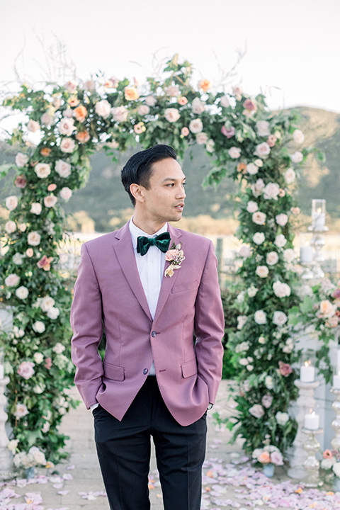 the groom in a pink suit coat, black pants, and a green velvet bow tie