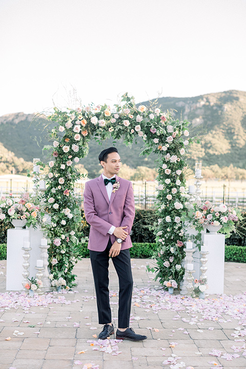groom in a pink suit coat with black pants and green velvet bow tie