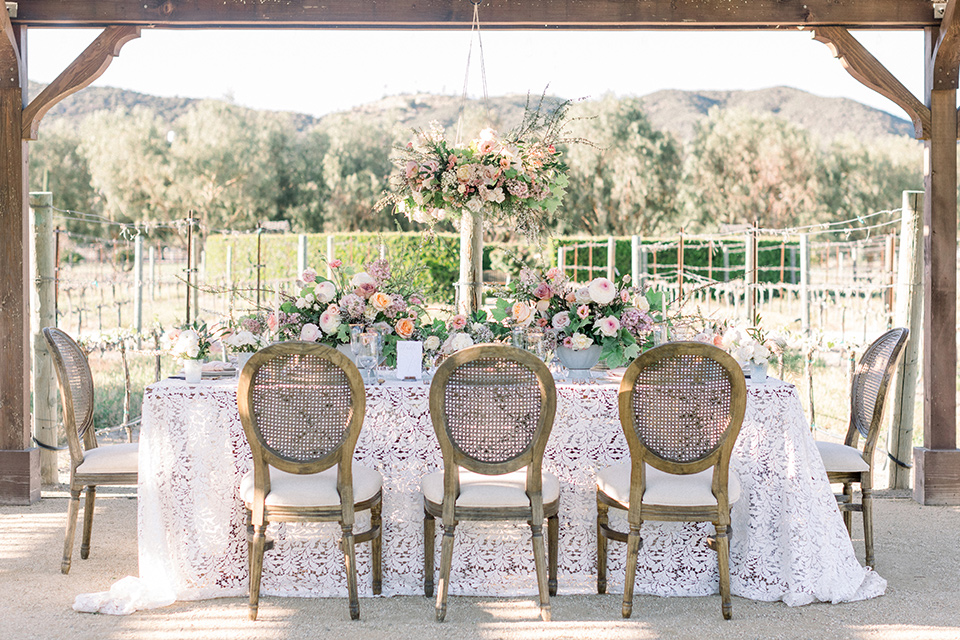 white and wooden chair and couch furniture with white linens and green floral arrangements
