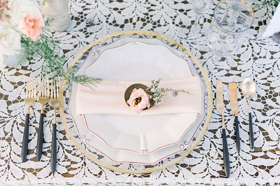 white plates and gold flatware and white floral linens