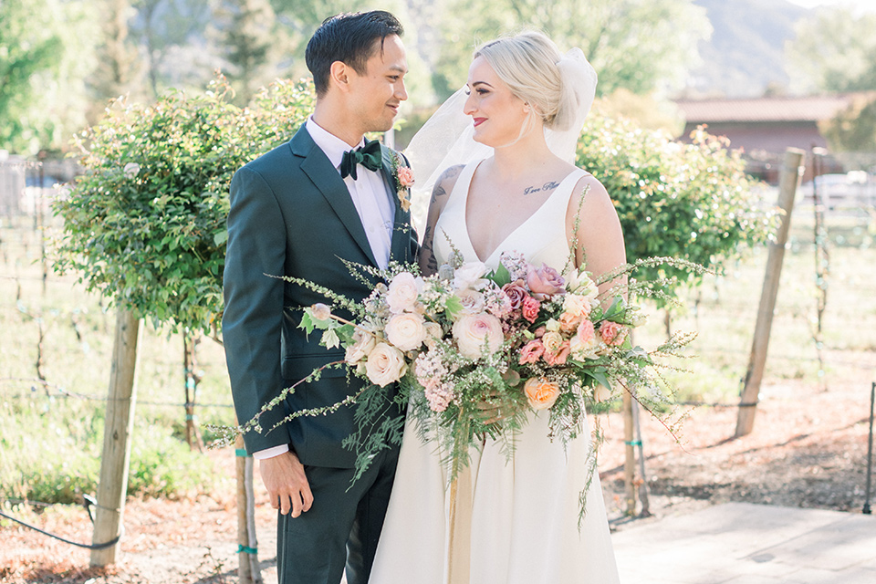 bride in white ballgown and groom in a green suit
