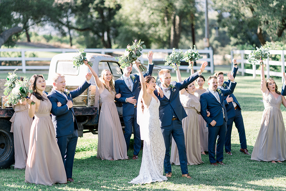 Circle-Oak-ranch-wedding-bridal-party-arms-raised-bridesmaids-in-taupe-colored-long-dresses-groomsmen-in-cobalt-blue-suits-with-floral-long-ties-bride-in-lace-form-fitting-gown-with-thin-straps-and-groom-was-in-a-cobalt-suit-with-a-floral-bowtie
