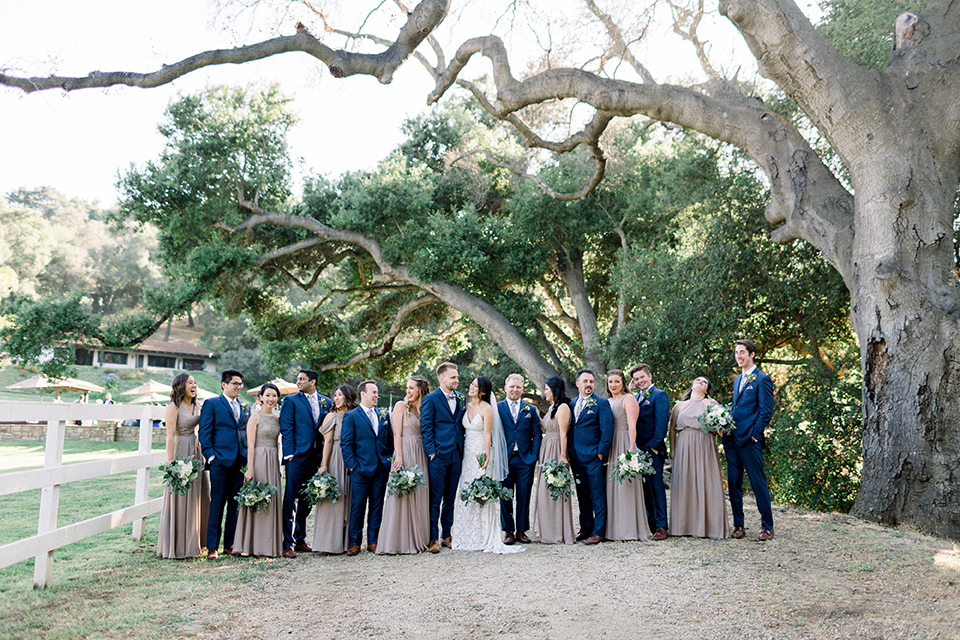 Circle-Oak-ranch-wedding-bridal-party-in-a-line-bridesmaids-in-taupe-colored-long-dresses-groomsmen-in-cobalt-blue-suits-with-floral-long-ties-bride-in-lace-form-fitting-gown-with-thin-straps-and-groom-was-in-a-cobalt-suit-with-a-floral-bowtie