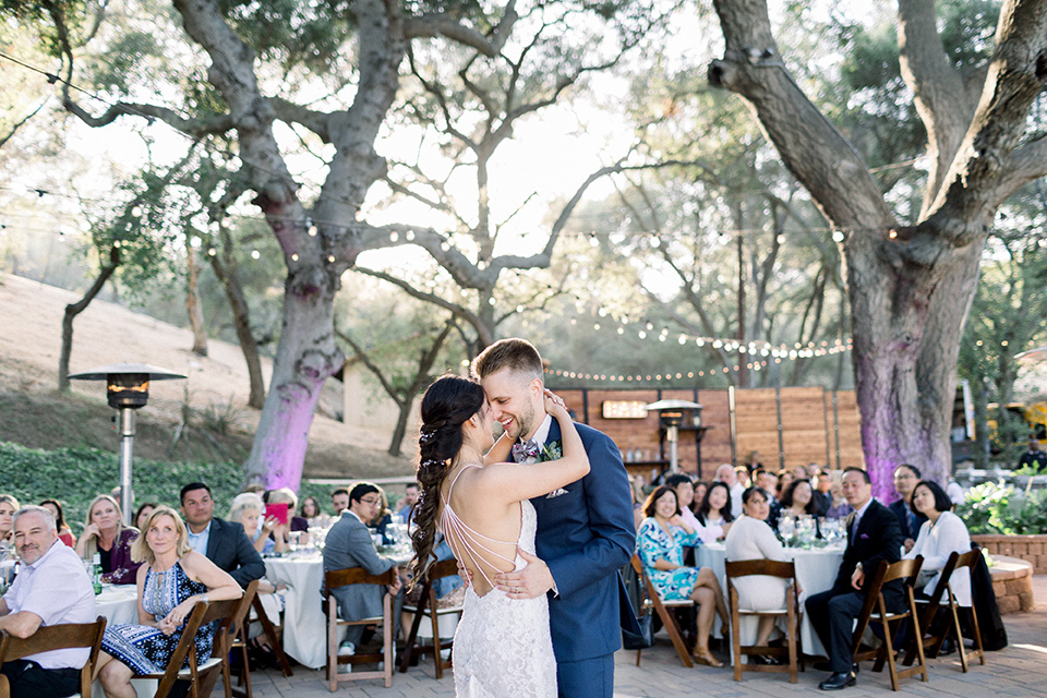 Circle-Oak-ranch-wedding-bride-and-groom-dancing-bride-in-lace-form-fitting-gown-with-thin-straps-and-groom-was-in-a-cobalt-suit-with-a-floral-bowtie