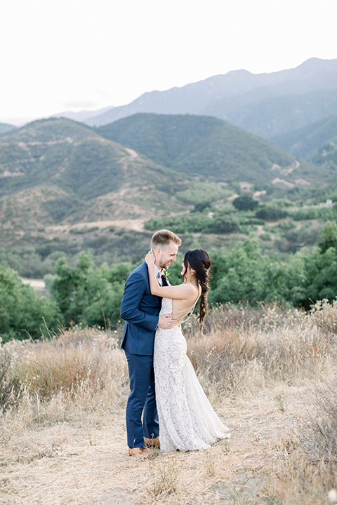 Circle-Oak-ranch-wedding-bride-and-groom-holding-each-other-with-views-in-the-background-bride-in-lace-form-fitting-gown-with-thin-straps-and-groom-was-in-a-cobalt-suit-with-a-floral-bowtie