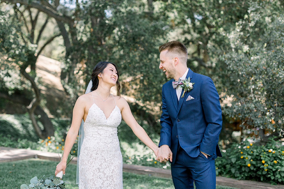 Circle-Oak-ranch-wedding-bride-and-groom-laughing-walking-bride-in-lace-form-fitting-gown-with-thin-straps-and-groom-was-in-a-cobalt-suit-with-a-floral-bowtie