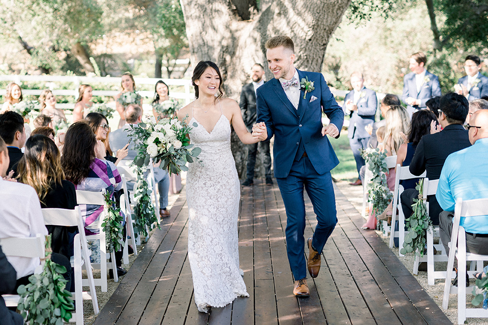 Circle-Oak-ranch-wedding-bride-and-groom-walking-down-aisle-bride-in-lace-form-fitting-gown-with-thin-straps-and-groom-was-in-a-cobalt-suit-with-a-floral-bowtie