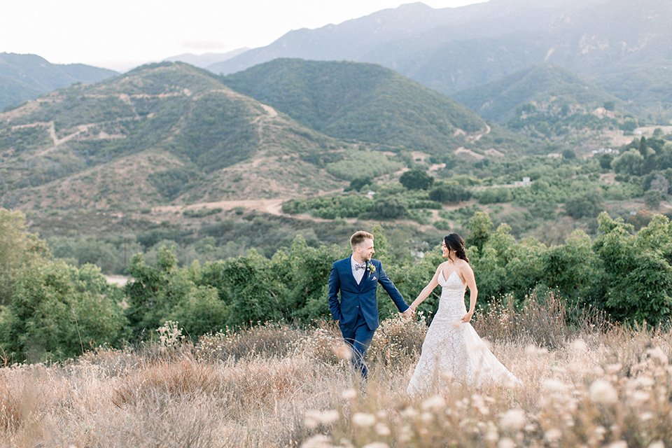 Circle-Oak-ranch-wedding-bride-and-groom-walking-bride-in-lace-form-fitting-gown-with-thin-straps-and-groom-was-in-a-cobalt-suit-with-a-floral-bowtie