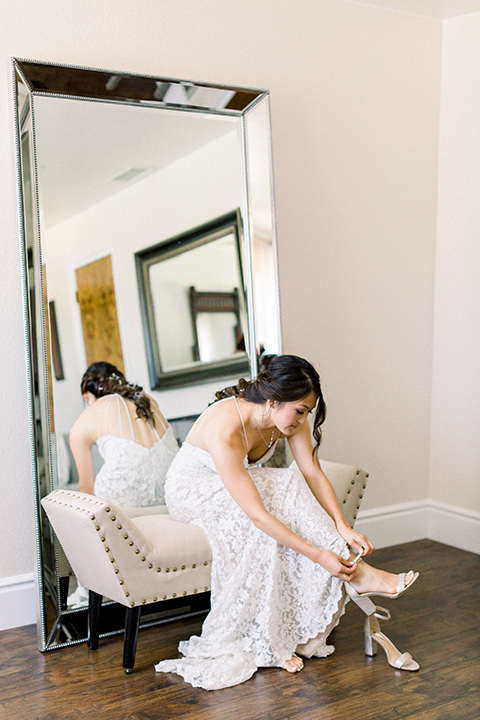 Circle-Oak-ranch-wedding-bride-putting-on-shoes-bride-in-lace-form-fitting-gown-with-thin-straps