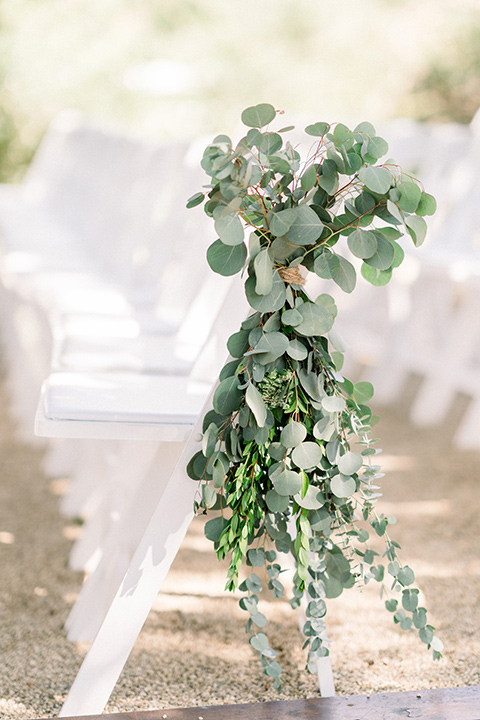 Circle-Oak-ranch-wedding-ceremony-chairs-with-greenry-on-it